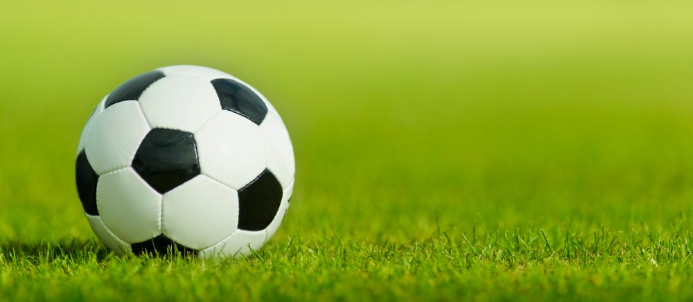 Soccer ball on grass with copy space